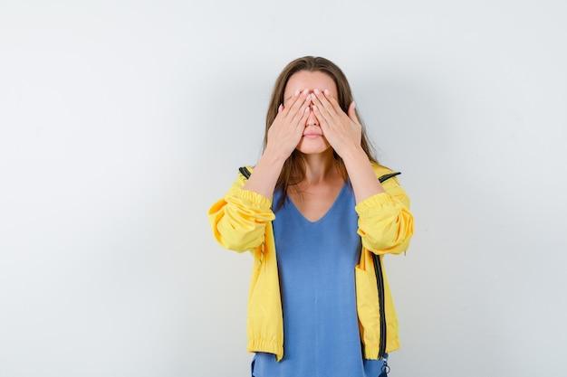Молодая леди, держась за глаза в футболке и выглядела спокойной, вид спереди.