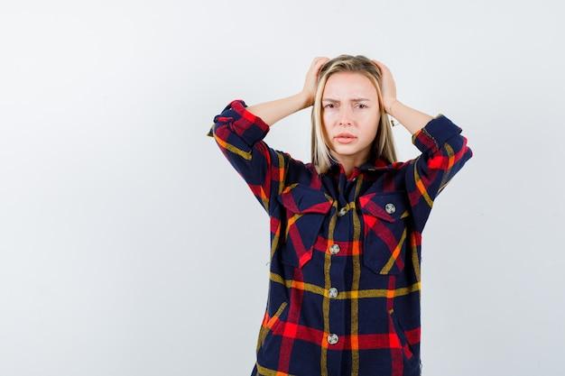 チェックのシャツで頭に手をつないで、忘れて見える若い女性。正面図。