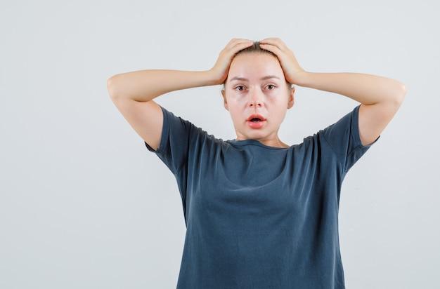 Девушка в серой футболке держит руки за голову и выглядит смущенной