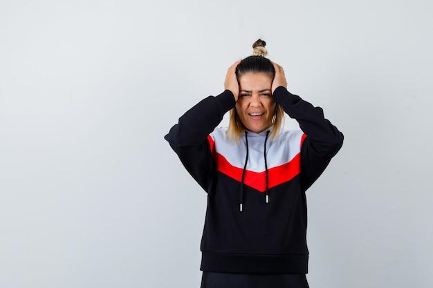 パーカーのセーターで頭に手をつないで、陽気に見える若い女性。