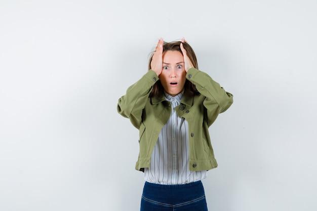 シャツ、ジャケットで頭に手をつないで、物欲しそうな正面図を探している若い女性。