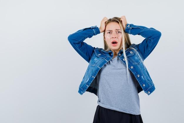 Tシャツ、デニムジャケット、スカートで頭に手をつないで、忘れて見える若い女性。