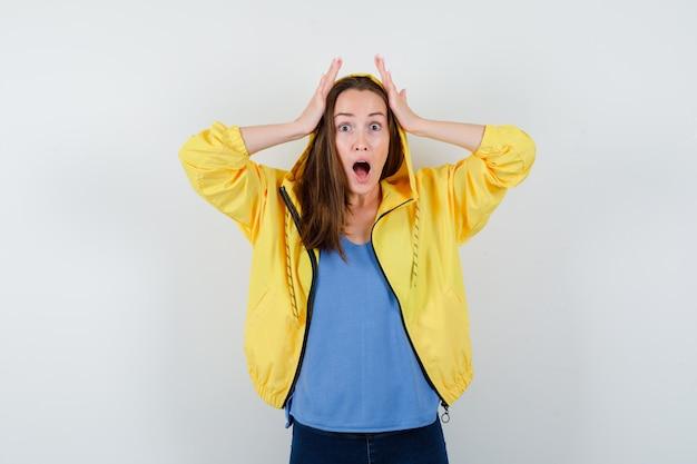 Tシャツ、ジャケットで頭に手をつないで、忘れて見える若い女性