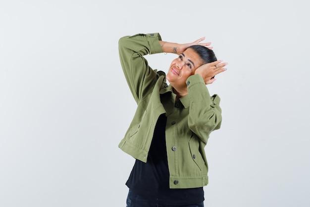 Tシャツで頭上に手を保持している若い女性