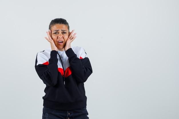 カラフルなスウェットシャツで彼女の頬に手をつないで、問題を抱えているように見える若い女性、正面図。