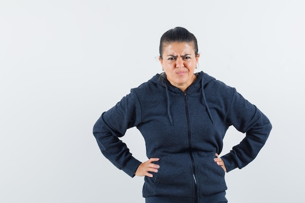 ジャケットに顔を酸っぱくし、不機嫌そうに見える間、彼女の腰に手をつないでいる若い女性。正面図。