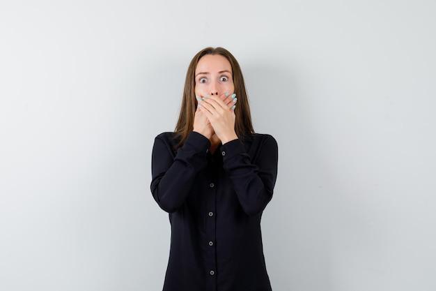 Молодая дама держится за рот и выглядит испуганной