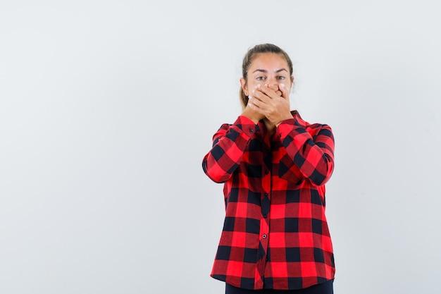 チェックシャツを着て口に手をつないでショックを受けている若い女性