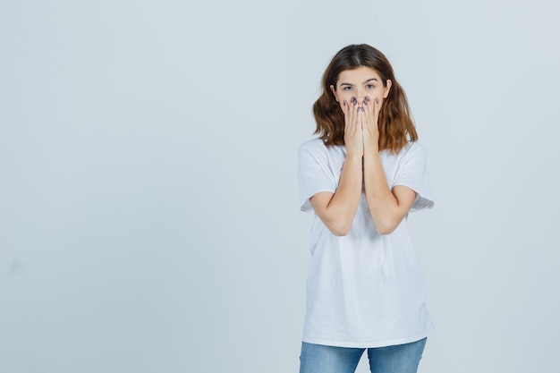 Tシャツ、ジーンズで口に手をつないで、驚いて見える若い女性。正面図。