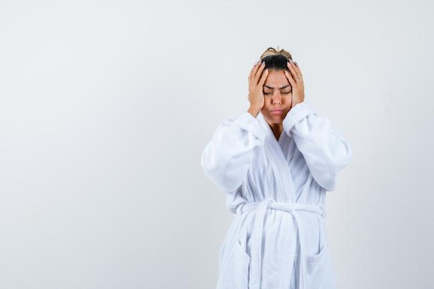 バスローブで寺院に手をつないで、疲れているように見える若い女性