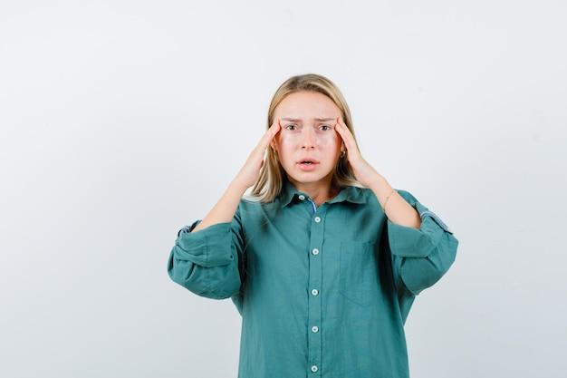 녹색 셔츠에 사원에 손을 잡고 우울 찾고 젊은 아가씨.