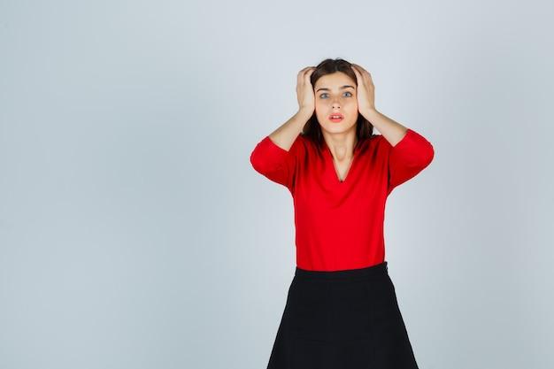 Молодая дама в красной блузке, черной юбке держится за виски и выглядит обеспокоенной