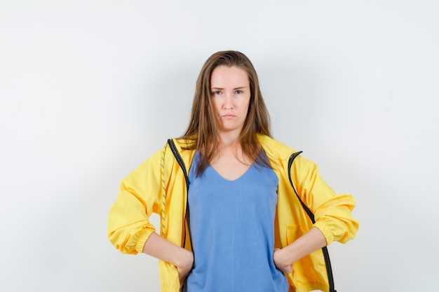 T- 셔츠, 재킷에 허리에 손을 잡고 짓궂은 찾고 젊은 아가씨