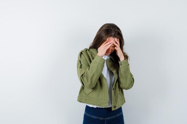 블라우스, 재킷에 머리 위로 손을 잡고 슬픈, 전면보기를 찾고 젊은 아가씨.