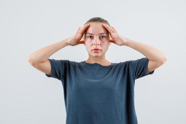 Девушка в серой футболке держит руки над головой и смотрит осторожно