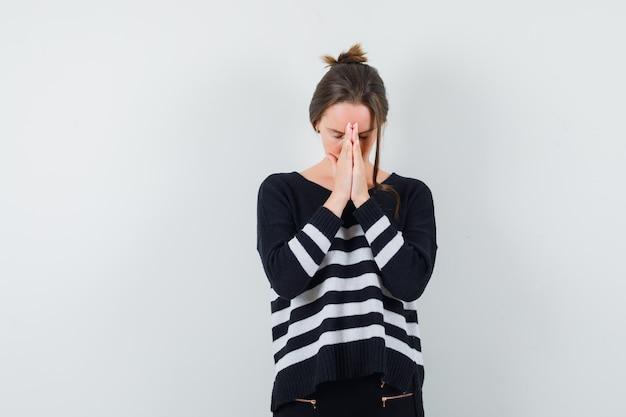 Giovane donna che si tiene per mano nel gesto di preghiera in camicia casual e sembra speranzoso