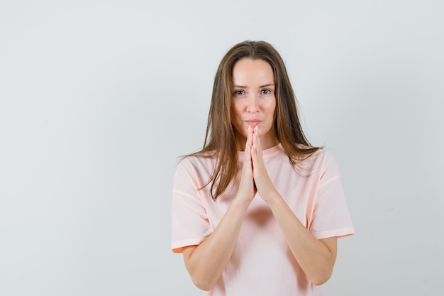 Young lady holding hands in praying gesture in pink t-shirt and looking hopeful