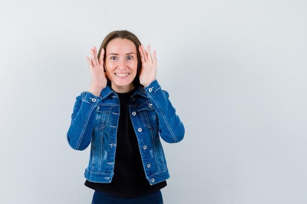 Giovane donna che si tiene per mano per vedere chiaramente in camicetta, giacca e sembra curiosa, vista frontale.