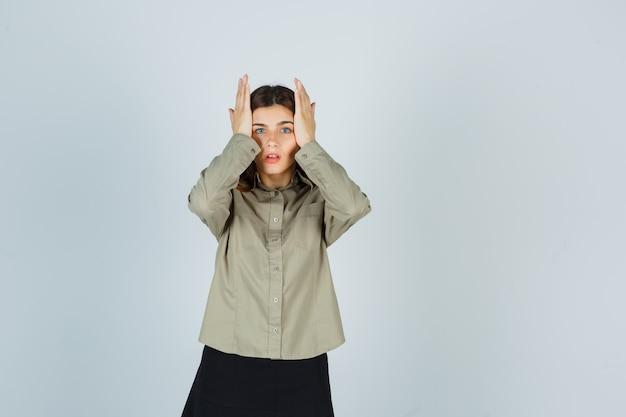 Giovane donna che tiene le mani sulle tempie in camicia, gonna e sembra perplessa