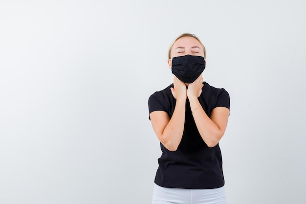Young lady holding hands on throat in t-shirt, pants, medical mask isolated