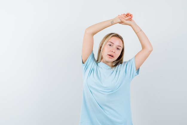 Giovane signora che tiene le mani insieme sopra la testa in maglietta e sembra affascinante. vista frontale.
