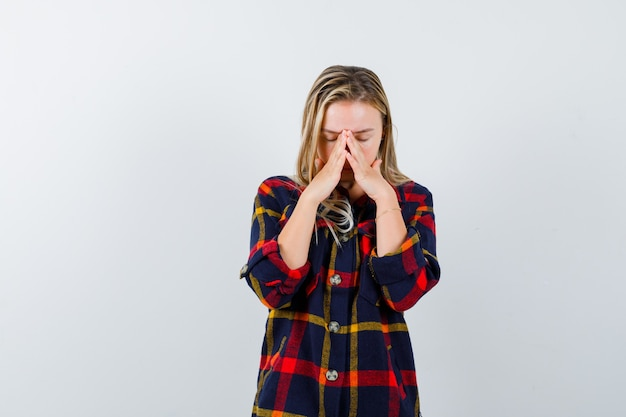 Young lady holding hands together on nose bridge in checked shirt and looking exhausted. front view.