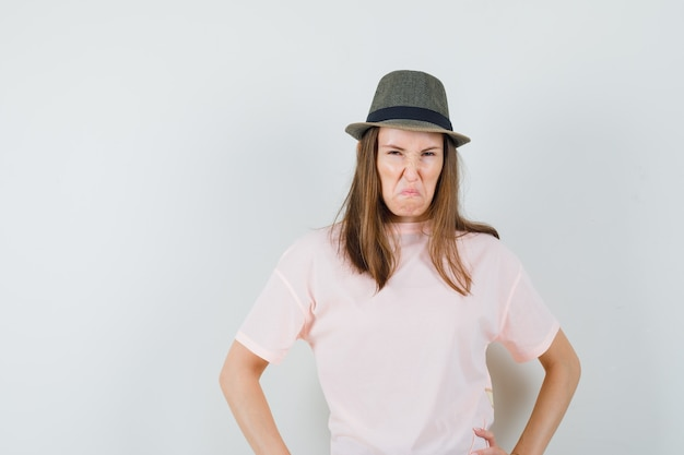 Young lady holding hands on waist in pink t-shirt hat and looking spiteful