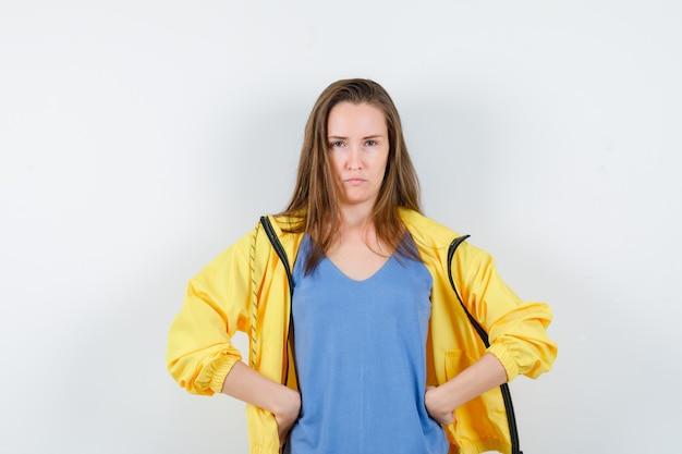 Giovane donna che si tiene per mano in vita in maglietta, giacca e sembra dispettosa