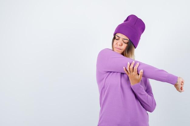 Giovane donna che tiene le braccia in maglione viola, berretto e sembra concentrata, vista frontale.
