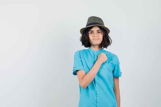 Giovane donna che tiene il pugno sul petto in camicia blu, cappello e aspetto maestoso.