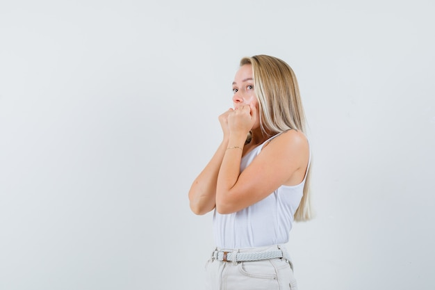 Young lady holding her fists on her mouth while looking aside in white blouse and looking uncomfortable