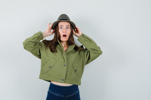 Young lady holding her hat in jacket pants and looking wondered