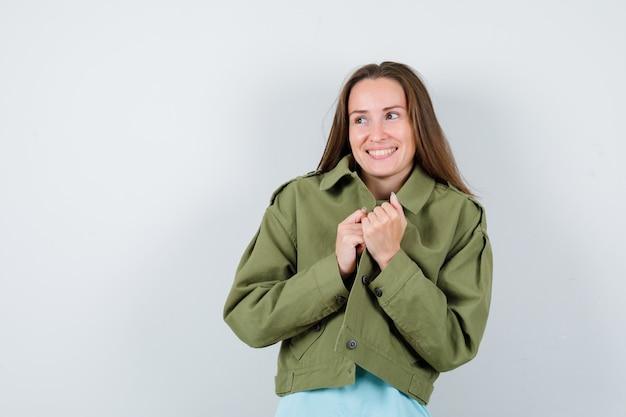 Tシャツ、ジャケットで目をそらし、陽気に見えながらジャケットを保持している若い女性。正面図。