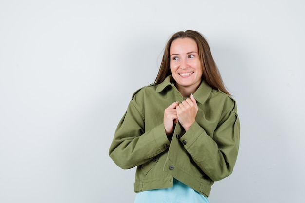 Young lady holding jacket while looking away in t-shirt, jacket and looking cheerful. front view.