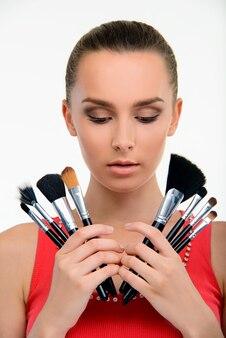 Молодая дама, держащая кисти для макияжа.