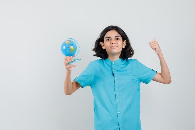 青いシャツで勝者のジェスチャーを示し、満足そうに見える間、ミニ地球儀を保持している若い女性。