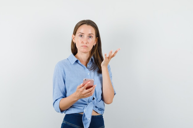 Young lady holding mobile phone in blue shirt, pants and looking confused.