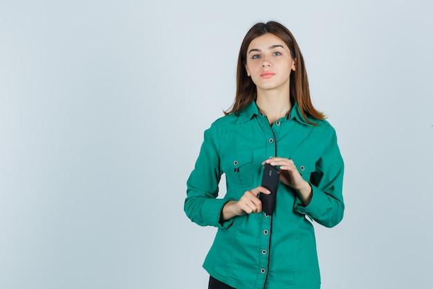 Giovane signora che tiene il telefono cellulare in camicia verde e sembra ragionevole. vista frontale.