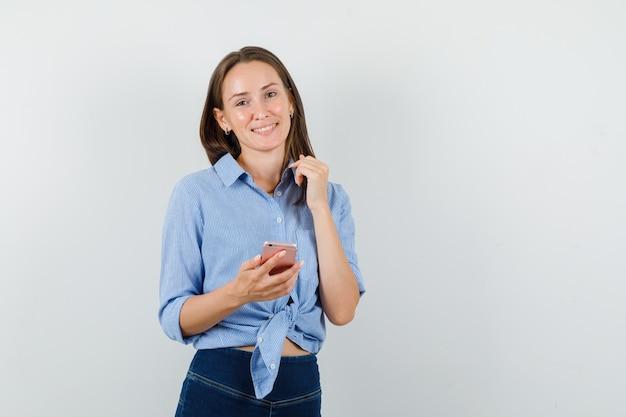 Молодая леди держит мобильный телефон в синей рубашке, штанах и выглядит весело