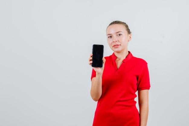 Молодая леди держит мобильный телефон в красной футболке и выглядит веселой