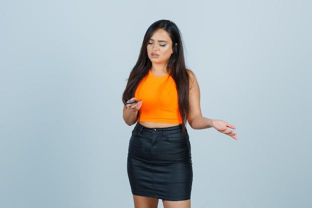 Молодая дама держит мобильный телефон в майке, мини-юбке и задумчиво. передний план.