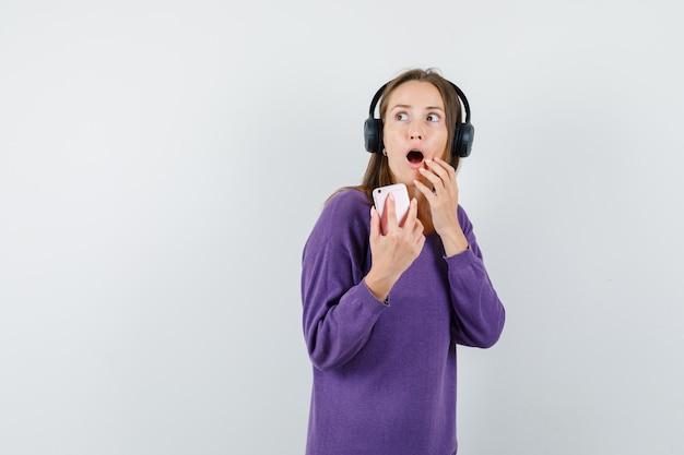Молодая леди держит мобильный телефон в фиолетовой рубашке и выглядит удивленным, вид спереди.