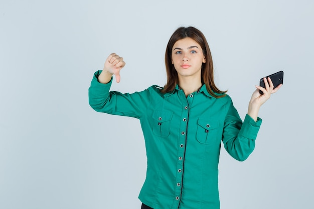 Young lady holding mobile phone, showing thumb down in green shirt and looking displeased , front view.