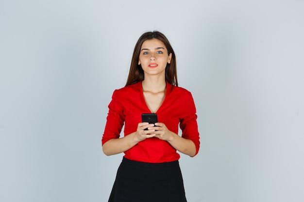 Giovane signora che tiene il telefono cellulare mentre guarda la fotocamera in camicetta rossa