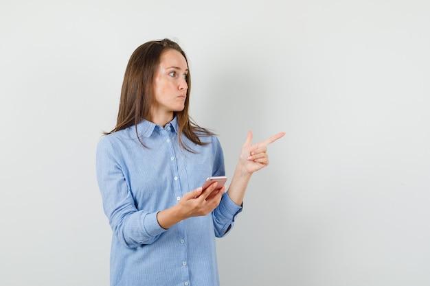Молодая дама держит мобильный телефон, указывая в синей рубашке и глядя сосредоточенным.