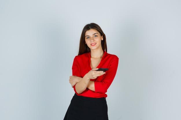 Молодая леди держит мобильный телефон, позирует в красной блузке, юбке и выглядит весело