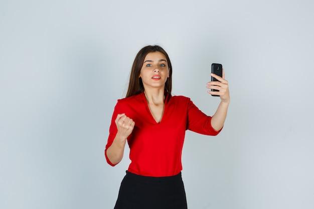 Молодая дама держит мобильный телефон, поднимая кулак в красной блузке