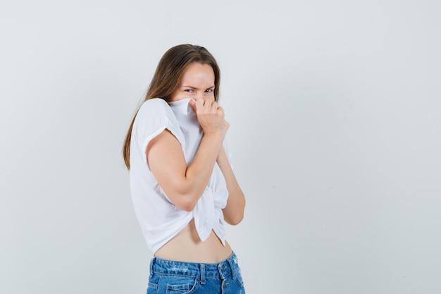Giovane donna che tiene la bocca con il suo colletto in camicetta bianca e sembra disgustata. vista frontale.
