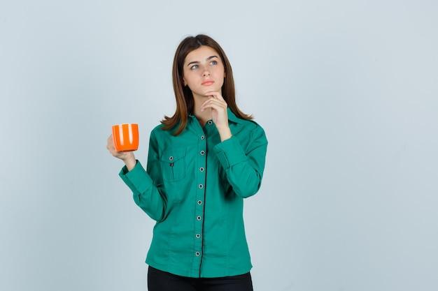 셔츠에 오렌지 컵 차를 들고 잠겨있는, 전면보기를 찾고 젊은 아가씨.