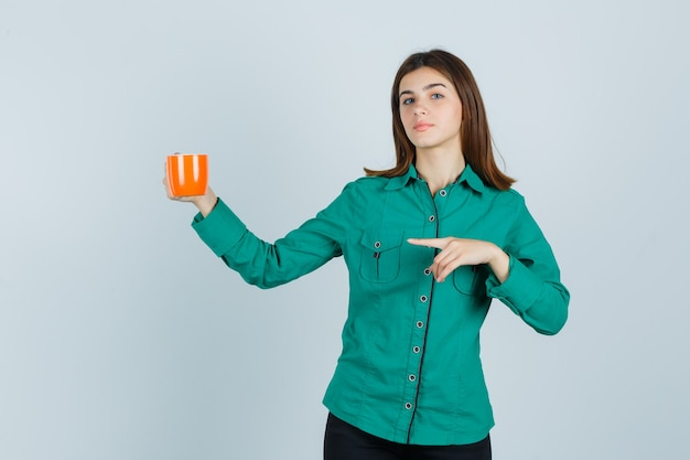 Young lady holding orange cup of tea, pointing to the left side in shirt and looking confident. front view.